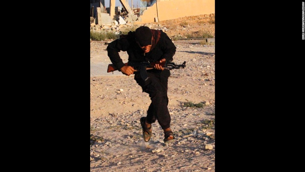 A Free Syrian Army fighter runs for cover in Raqqa province on September 8.