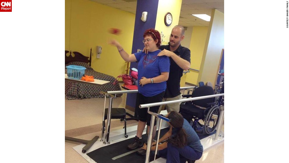 Emily throws bean bags while standing at a therapy session on September 3, a week after she returned to school.