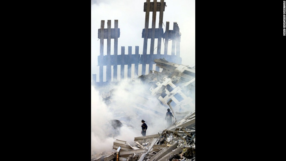 Firefighters stand in the smoldering wreckage of the World Trade Center on September 13, 2001.