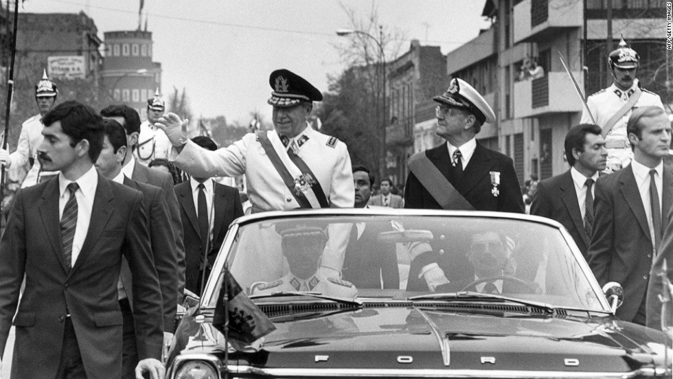 General Augusto Pinochet, standing in a white jacket, a career army officer, led the military coup and established himself as the head of the ensuing government. He waves from the motorcade on September 11, 1973 in Santiago, accompanied by the Chilean defense minister, Vice-admiral Patricio Carvajal. A year later, in 1974, Pinochet signed a decree naming himself Chilean president.