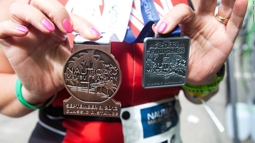 """Timme shows off her two medals after finishing the triathlon. At 58, Timme is the oldest member of the Fit Nation team, and she's proven <a href=""""http://www.cnn.com/2013/08/16/health/fit-nation-timme-bike-commute/index.html"""">age is just a number</a>. """"As I crossed the finish line, I remember telling myself that I had actually accomplished something that I honestly didn't think I had the physical or mental strength to do. At that moment, I felt like I could do anything!"""""""