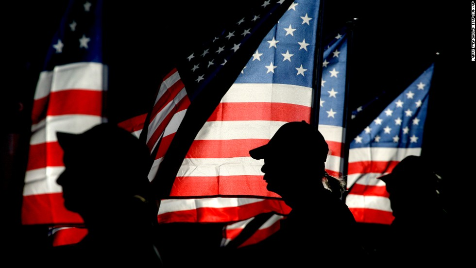Patriot Guard rider and U.S. Navy veteran Ron Connally, center, of Oak Harbor, Washington, holds a flag during a ceremony in Bremerton on September 11.