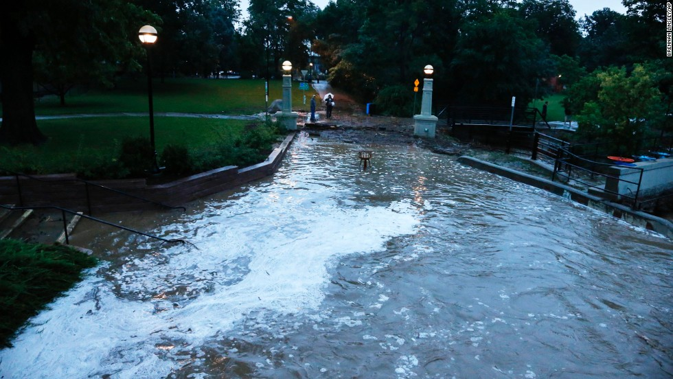 Flash flood waters rush over a walking path in downtown Boulder on September 12.