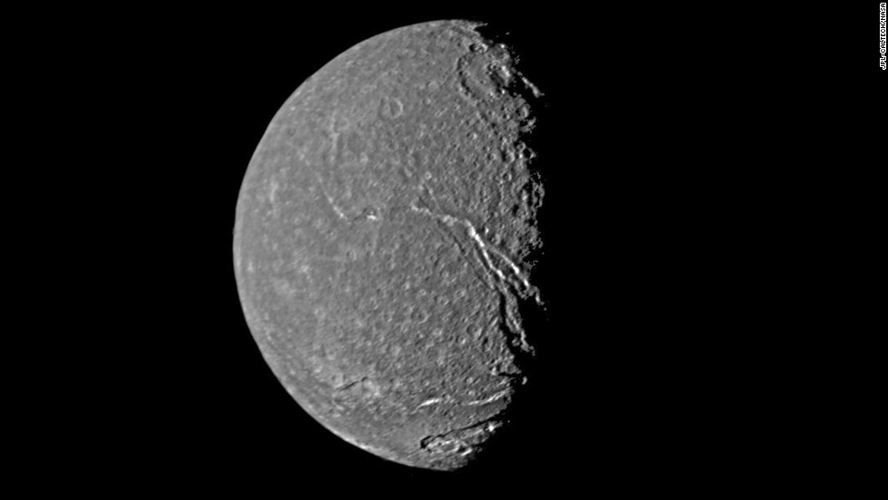 Uranus' moon Titania shows a crater-pocked surface as well as prominent fault valleys that stretch across the moon.