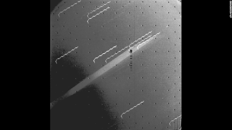 Voyager 1 captured the first evidence of a ring around the planet Jupiter. The multiple exposure of the extremely thin faint ring appears as a broad light band crossing the center of the picture. The background stars look like broken hairpins because of spacecraft motion during the 11-minute  exposure. The black dots are geometric calibration points in the camera.