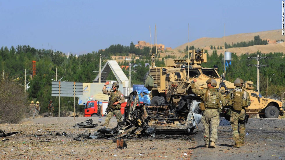 U.S. military forces observe the wreckage of a car bomb near the U.S. consulate in Herat, Afghanistan, on Friday, September 13. Seven heavily armed Taliban suicide attackers struck the consulate, setting off two car bombs and sparking a shootout with U.S. forces.