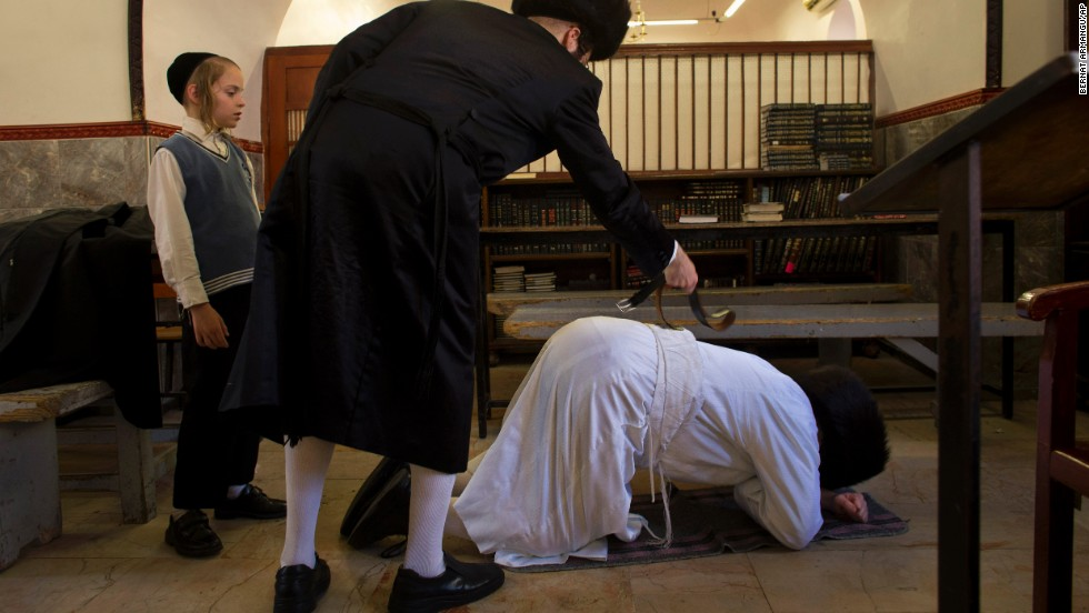 An ultra-Orthodox Jewish man whips another ultra-Orthodox Jew with a leather strap as a symbolic punishment for his sins during the traditional Malkot ceremony, ahead of Yom Kippur, in Jerusalem on September 13.