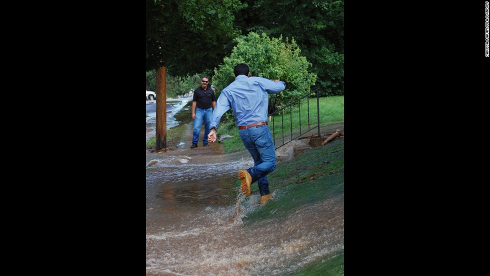 A man runs through the floodwaters in a yard in Boulder on September 13.
