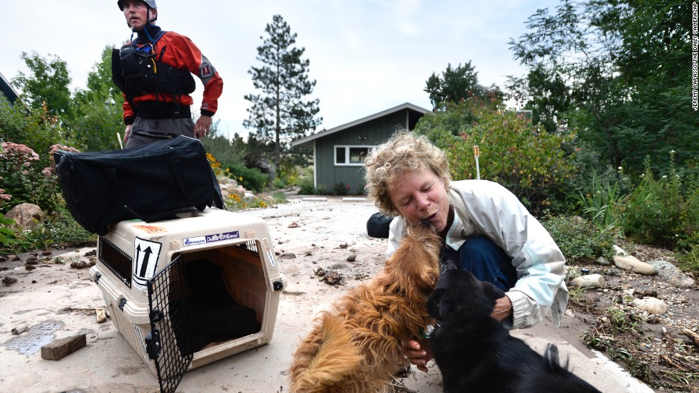 Suzanne Sophocles hugs her dogs after they were rescued from her flooded home on September 13 in Boulder. Thousands of people stranded by the flood waters in Colorado were finally able to come down by trucks and helicopters, two days after seemingly endless rain turned normally scenic rivers and creeks into coffee-colored rapids that wrecked scores of roads and wiped out neighborhoods.