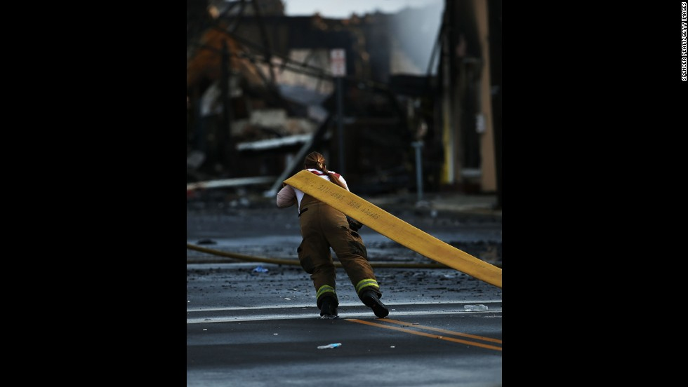 A firefighter pulls a fire hose  on September 13. About 100 firefighters were still handling hot spots Friday and mopping up, said Ocean County Fire Administrator Brian Gabriel.