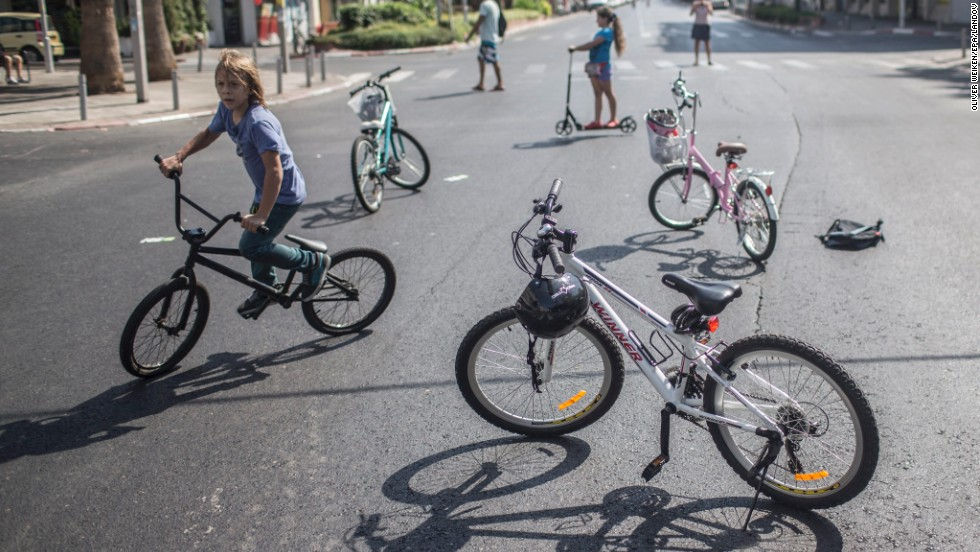 Israeli children ride their bikes on an empty street during Yom Kippur in Tel Aviv on September 14.