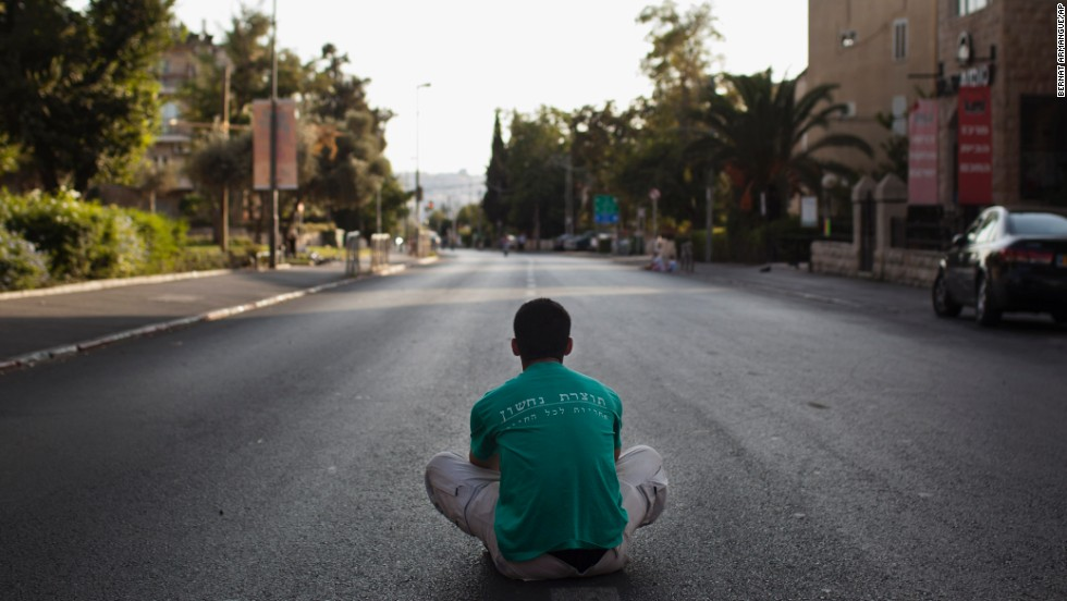 An Israeli man sits in the middle of an empty street during Yom Kippur in Jerusalem on September 14. During the holiday, the streets in Israel's cities are nearly empty in respect of the holiday. Businesses, public transportation and even Israeli television and radio broadcasts are suspended, according to Israel's tourist information website.