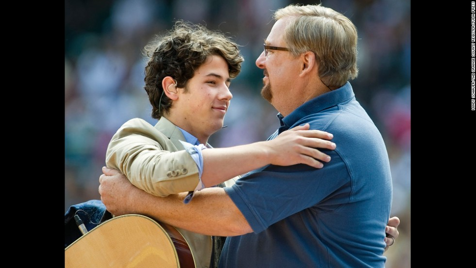 Nick Jonas of the Jonas Brothers embraces Warren after a short performance with his brothers during the church's 30th anniversary Easter services at Angel Stadium in Anaheim, California, on April 4, 2010.