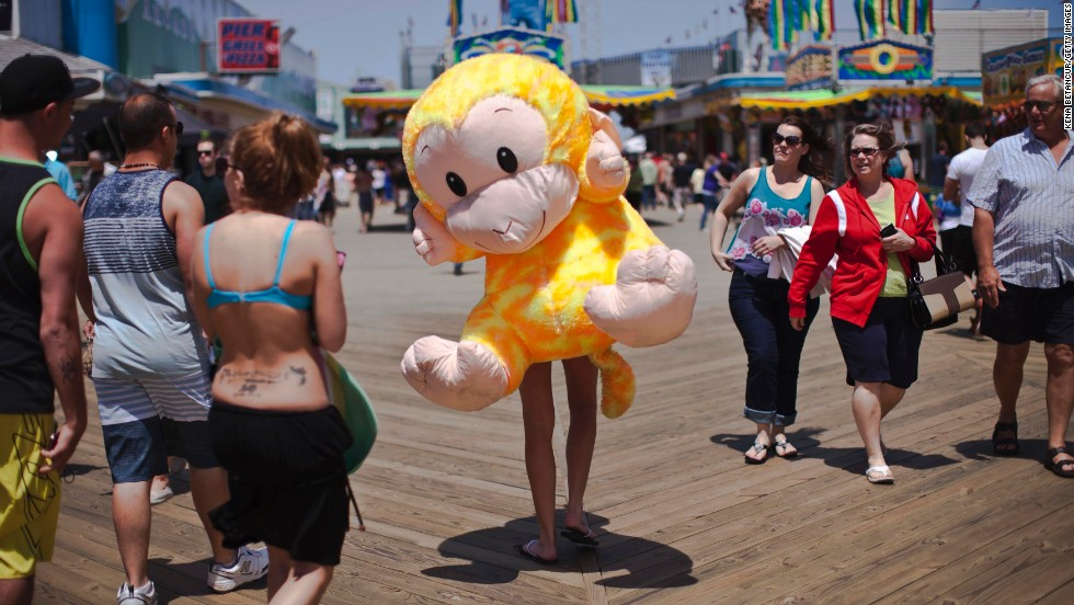 A woman carries a stuffed monkey on her back on the boardwalk in Seaside Heights the first weekend Jersey Shore beaches reopened on May 27.