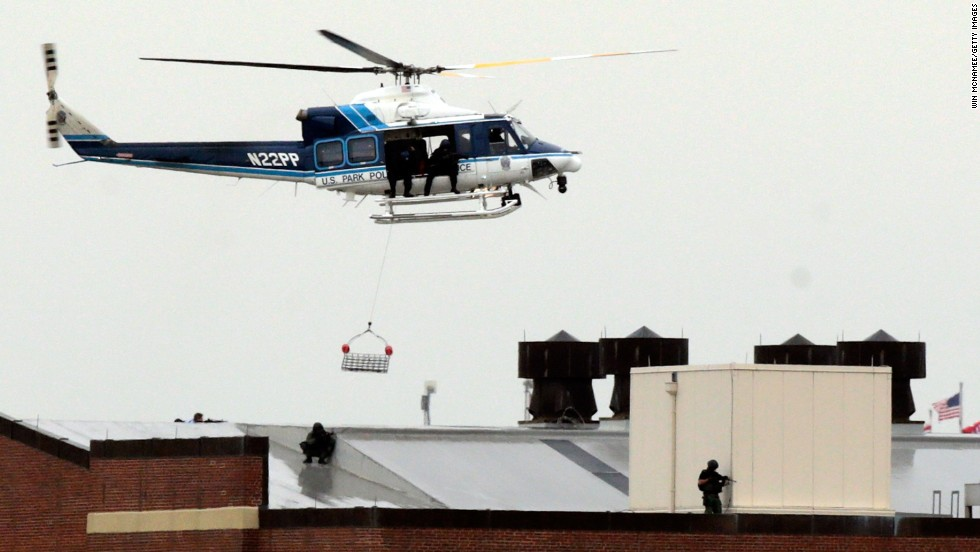 A police helicopter hovers above snipers on the roof of a building at the Washington Navy Yard.