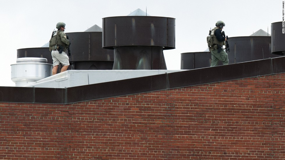 "Police officers walk on a rooftop at the Washington Navy Yard on September 16, 2013, after a <a href=""http://www.cnn.com/2013/09/16/us/dc-navy-yard-gunshots/index.html"">shooting rampage</a> in the nation's capital. At least 12 people and suspect Aaron Alexis were killed, according to authorities."