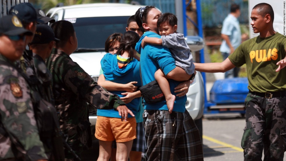 A two-year-old boy is carried by his father after a rescue mission by state security forces from Muslim rebels following an assault on September 17.