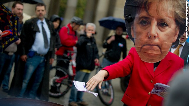 A person wearing an Angela Merkel mask throws fake euros at an anti-euro Alternative for Germany (AfD) rally.
