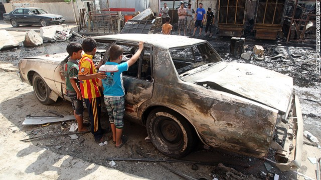 Children inspect a burned-out car after a car bomb exploded the previous day in Mashtal on September 16, 2013.