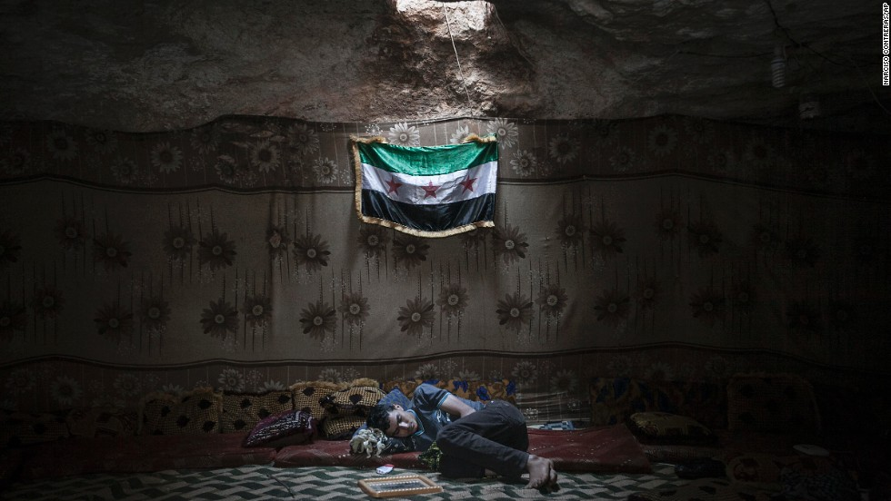 A Free Syrian Army fighter rests inside a cave at a rebel camp in Idlib province on Tuesday, September 17.