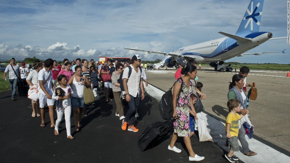 People prepare to board a flight to Mexico City at an airport in Acapulco on September 17.