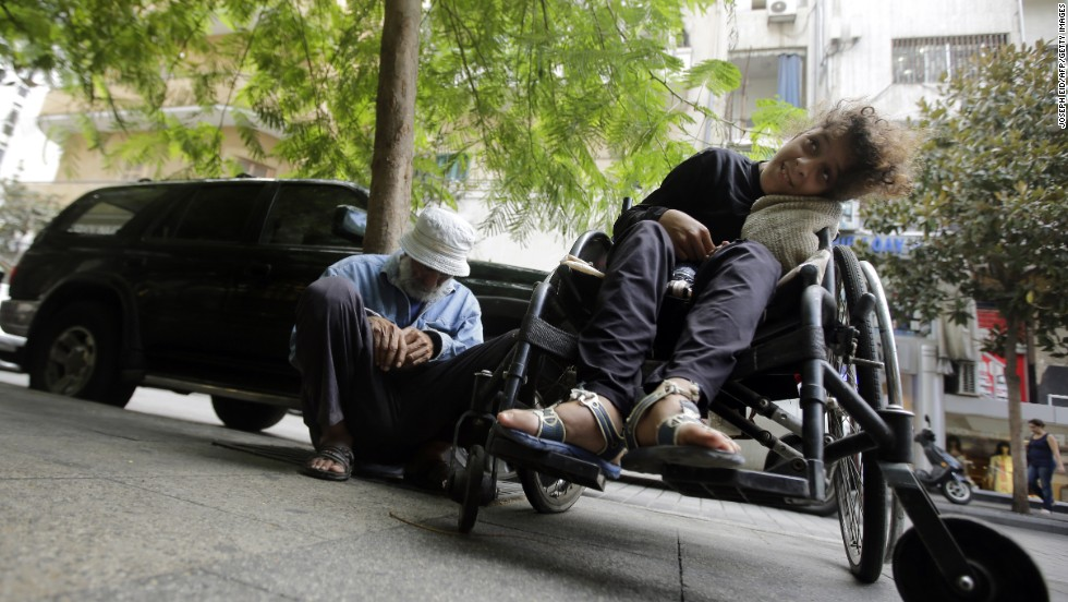 Two Syrian refugees sit on a Beirut street in September 2013.