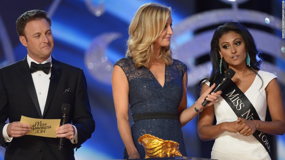 ATLANTIC CITY, NJ - SEPTEMBER 15: Miss America 2014 contestant Miss New York Nina Davuluri (R) performs in the questions portion with co-hosts TV personalities Chris Harrison (L) and Lara Spencer during the Miss America Competition at Boardwalk Hall Arena on September 15, 2013 in Atlantic City, New Jersey.