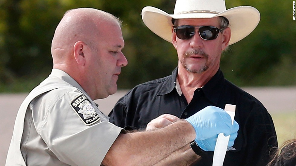 Tim Porter, right, talks with Beckham County Sheriff's Deputy J. Kessel after giving a DNA sample at the scene in September 2013. Porter believed his grandfather's remains were in one of the cars.