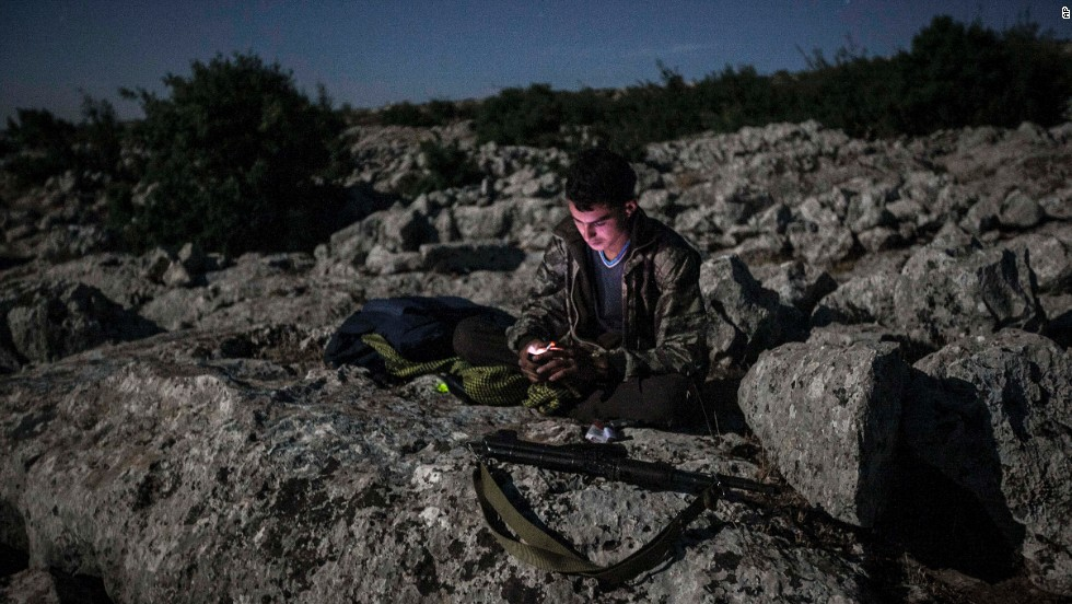 A Syrian opposition fighter takes a break on a mountain near a rebel camp in Idlib province on September 18.