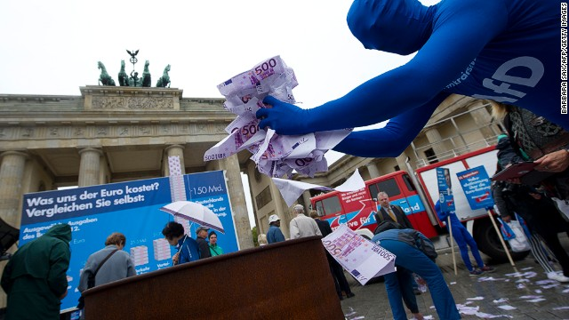 Fake euro notes are thrown onto a fire at a rally for anti-euro party Alternative for Germany (AfD) at Berlin's Brandenburg Gate.