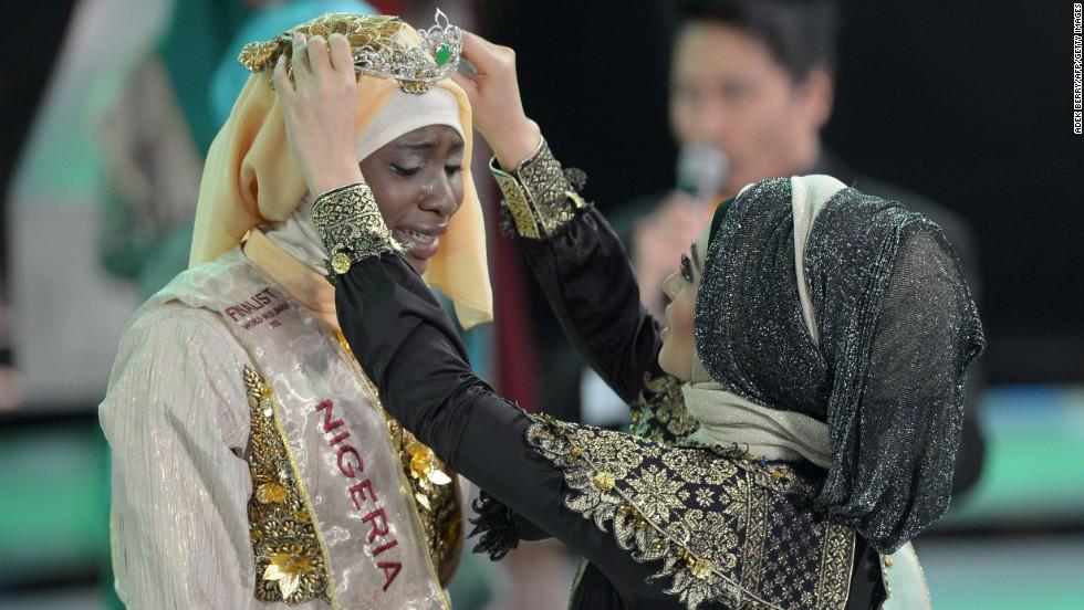 Ajibola is crowned by Nina Septiani, World Muslimah 2012 winner.
