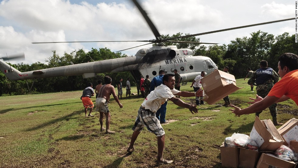 People unload boxes of food from a Mexican navy helicopter in Acapulco on September 18.
