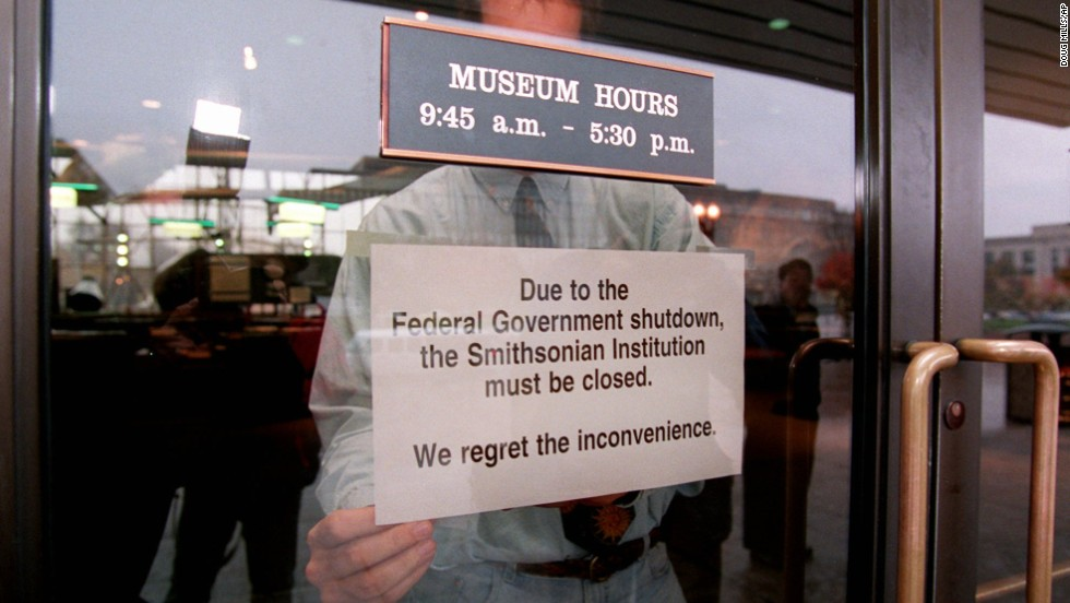 An employee hangs a sign on the door of the Smithsonian's National Air and Space Museum in Washington on November 14, 1995, marking the start of the government shutdown.