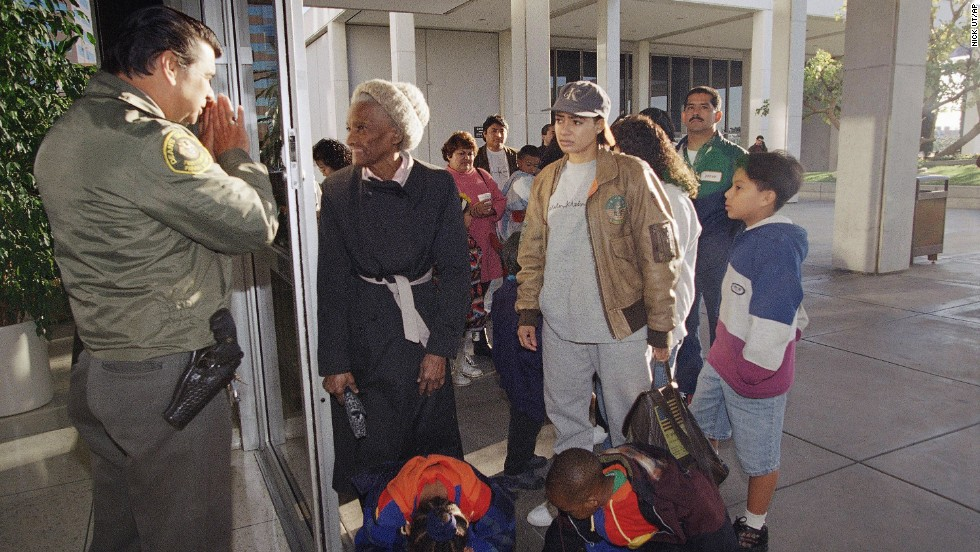 A security guard informs people that the passport office is closed at the Federal Building in Los Angeles on December 18, 1995.