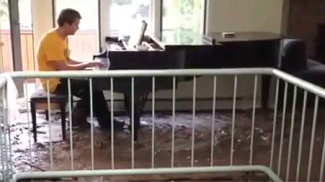 Man plays piano in flood-damaged home