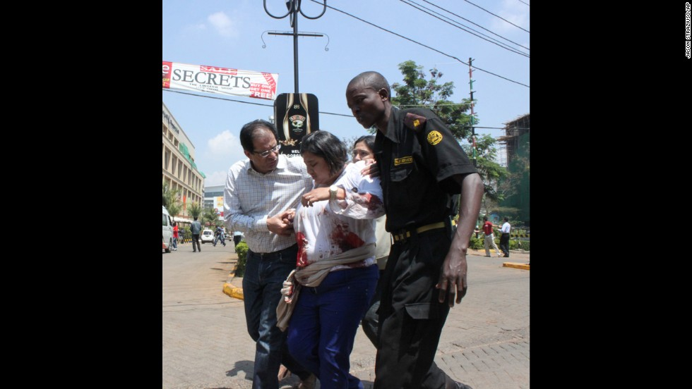 A security officer helps a wounded woman outside.