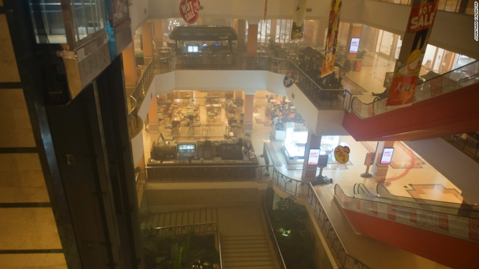 A body is seen on the floor inside the smoke-filled four-story mall.