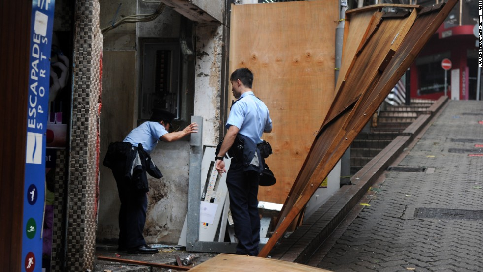 Police officers check for damage caused by Typhoon Usagi at a construction site in Hong Kong on September 23.