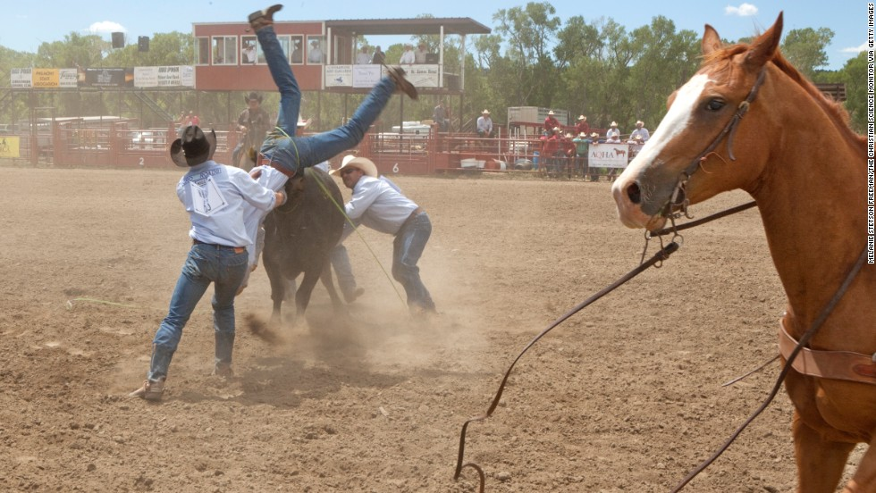 "A team of cowboys try to control a cow during the wild cow milking event at the Maverick Ranch Rodeo in Cimarron. Like many villages west of the Mississippi, Cimarron, in the northeast corner of the state, staked its claim as the ""Cowboy Capital of the World."""