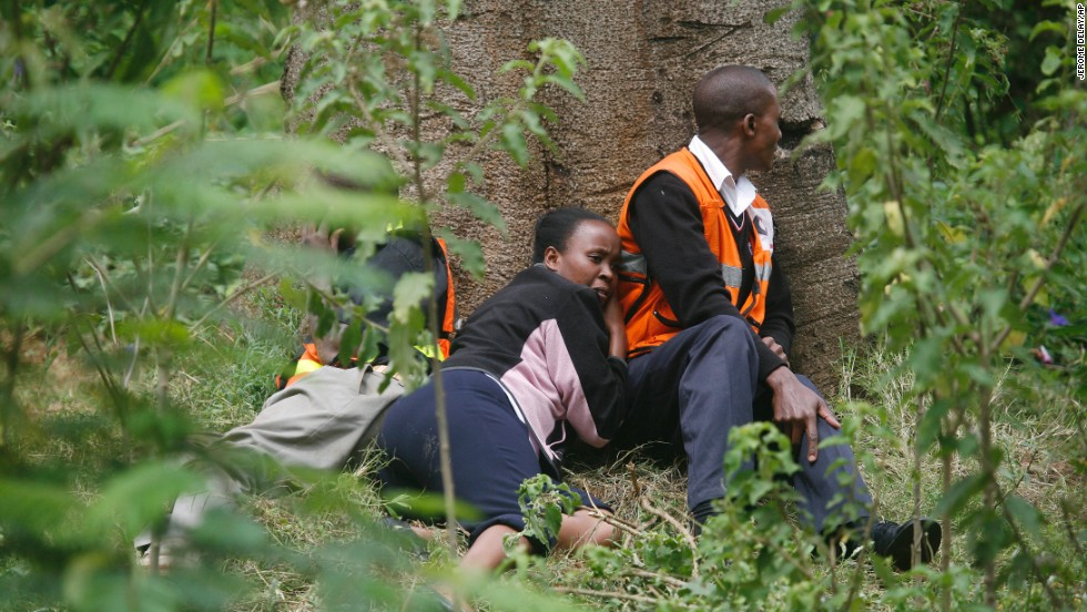Medics take cover behind a tree as gunfire and explosions are heard from the Westgate Mall on September 23.