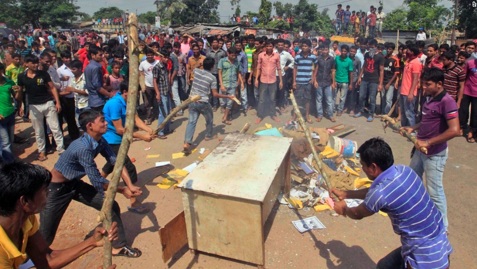 Garment workers beat furniture on a street during a protest in Gazipur, Bangladesh, on Monday, September 23. Thousands of workers, demanding higher pay, clashed with police on Monday.