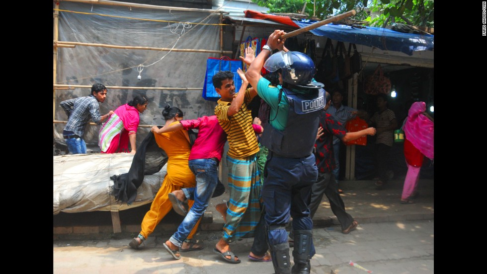 Protesters clash with a police officer in Dhaka, the capital of Bangladesh, on September 23.
