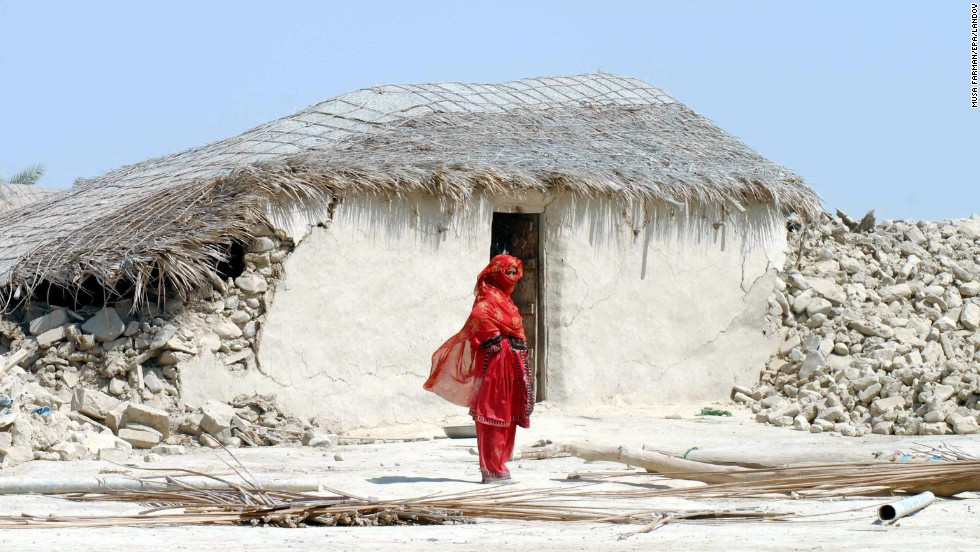 A woman stands in front of the rubble of her destroyed home in Balochistan province on September 25.