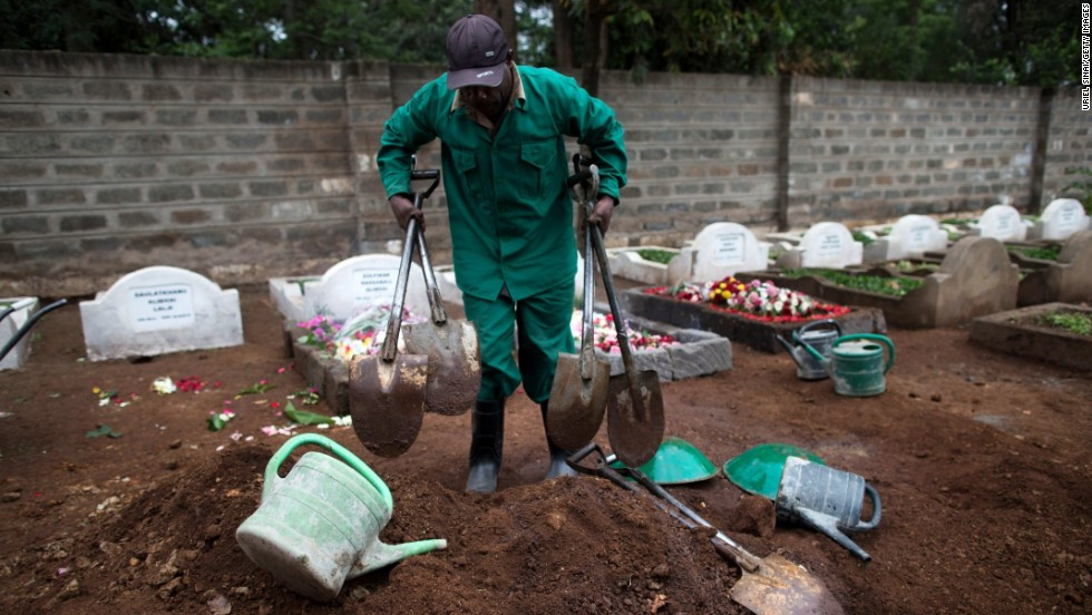 A cemetery worker gathers his tools after a funeral on September 25.