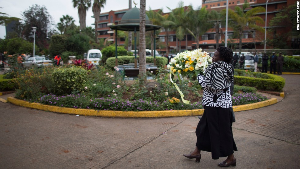 A Kenyan woman brings flowers to a funeral on September 25.