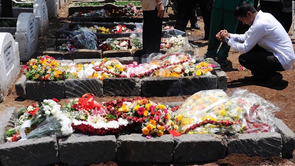 An Indian man prays on September 26 by the grave of Kenyan journalist Ruhila Adatia Sood, who was killed by gunmen at the Westgate mall, during her funeral in Nairobi.