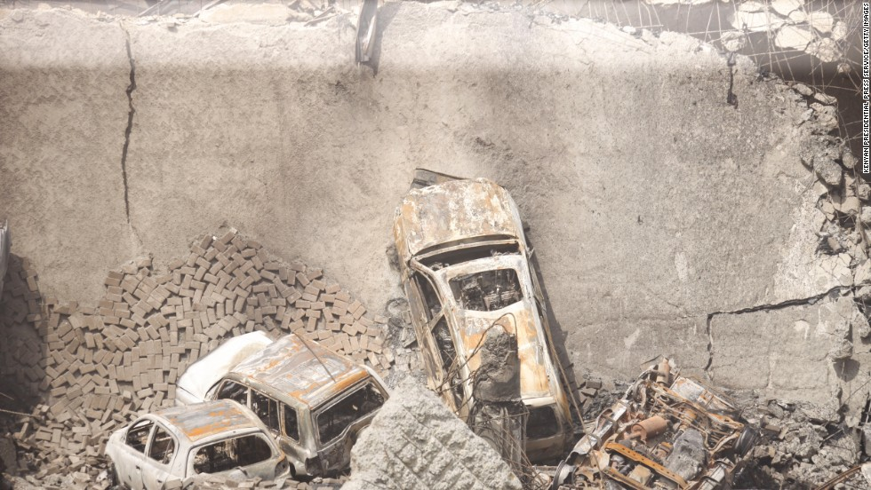 Cars sit amid the rubble of the collapsed structure.