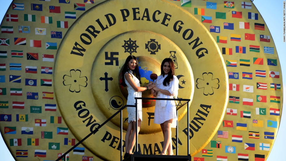 Miss World 2012 Wenxia Yu of China (left) and Miss Indonesia Vania Larissa (right) prepare to hit the World Peace Gong as Miss World contestants visit Kertalangu Cultural Village in Denpasar on Indonesia's resort island of Bali on September 21.