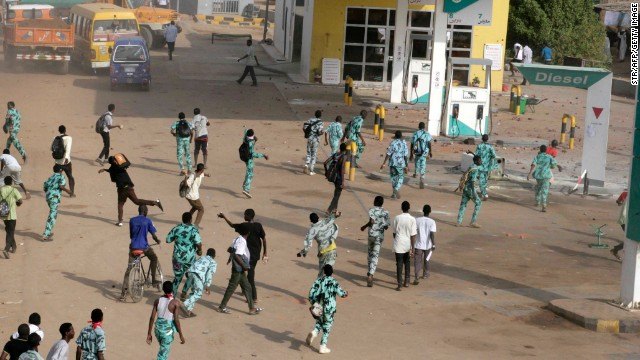 Sudanese protesters throw stones at a gas station in Khartoum's twin city of Omdurman on Wednesday.