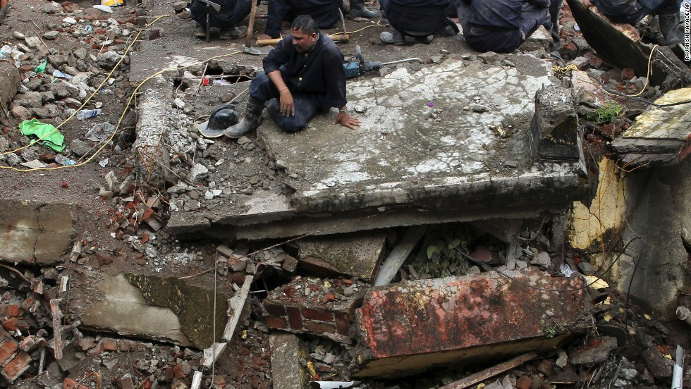 A rescue worker rests at the site of a collapsed building in Mumbai, India, on Saturday, September 28. The five-story building collapsed Friday, September 27, killing 66. Authorities believe a central wall and support beams were removed without permission, causing the collapse.